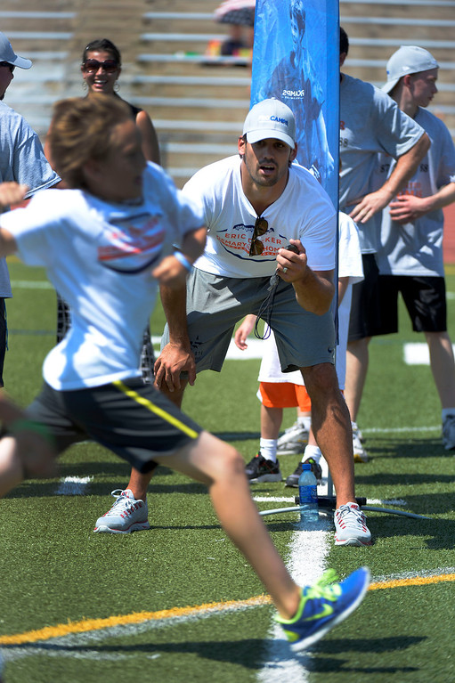 . Blake Kuykendall 10, crosses the finish line as Eric Decker times him during a race at camp. Demaryius Thomas and Eric Decker team up with ProCamps for their football camp held at Littleton High School July 11, 2013. (Photo By John Leyba/The Denver Post)