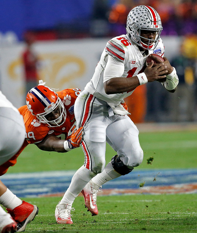 . Ohio State quarterback J.T. Barrett (16) eludes the reach of Clemson defensive end Clelin Ferrell (99) during the first half of the Fiesta Bowl NCAA college football playoff game, Saturday, Dec. 31, 2016, in Glendale, Ariz. (AP Photo/Ross D. Franklin)