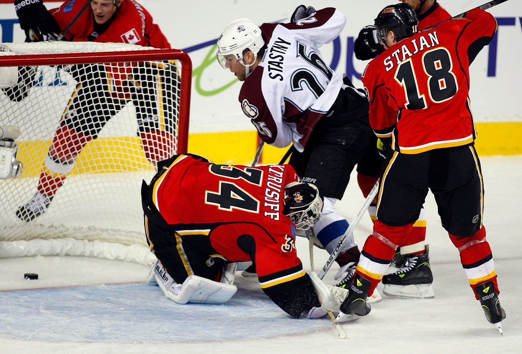 . Colorado Avalanche\'s Paul Stastny, top center, scores as Calgary Flames goalie Miikka Kiprusoff, left, from Finland, sprawls on the ice Matt Stajan watches during the third period of an NHL hockey game Thursday, Jan. 31, 2013, in Calgary, Alberta. The Avalanche won 6-3. (AP Photo/The Canadian Press, Jeff McIntosh)