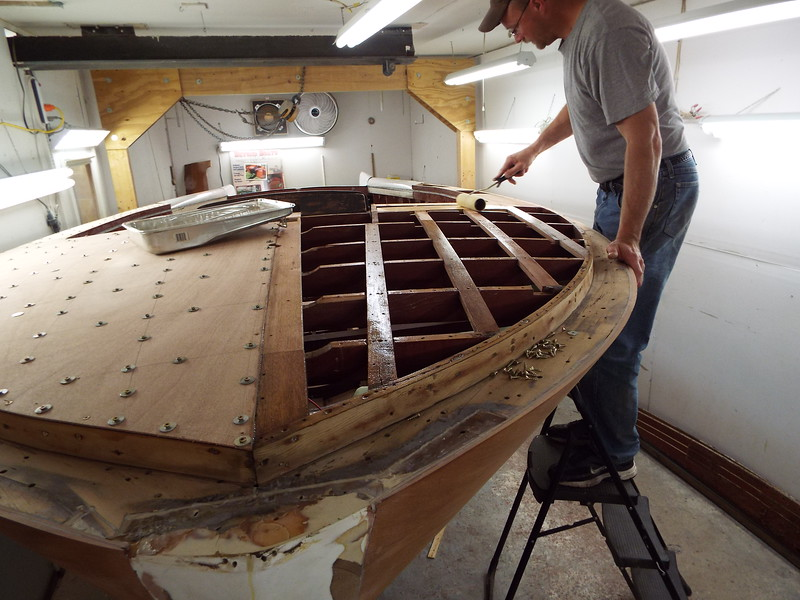 Applying epoxy to the port side front deck so the plywood skin can be installed.
