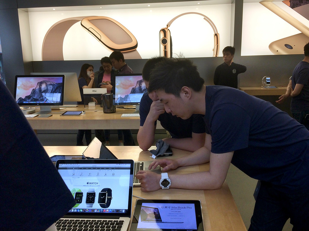 . Staff members attend to customers near a display about Apple Watch at an Apple retail store in Beijing, Friday, April 10, 2015. From Beijing to Paris to San Francisco, the Apple Watch made its debut Friday. Customers were invited to try them on in stores and order them online. China was among countries where the watch had its global debut Friday, reflecting the country\'s fast-growing status as one of Apple\'s most important markets. (AP Photo/Ng Han Guan)