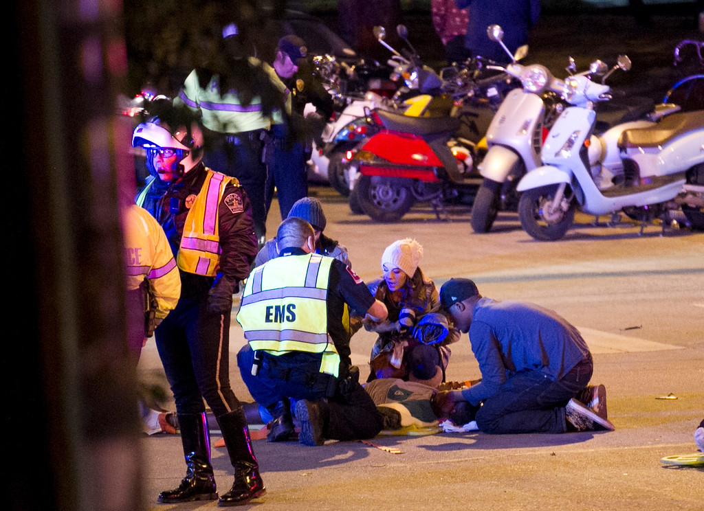 . Bystanders and a paramedics tend to people who were struck by a vehicle on Red River Street in downtown Austin, Texas, at SXSW on Wednesday March 12, 2014.  (AP Photo/Austin American-Statesman, Jay Janner)