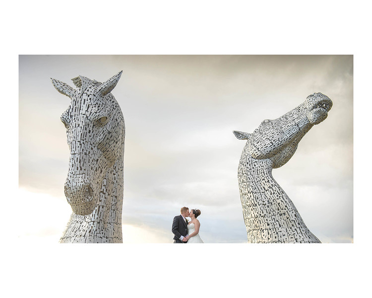 Wedding Photography of Nina & Scott, Grange Manor Hotel, Grangemouth, Falkirk, Photograph is of the Bride & Groom standing in front of the Andy Scott designed Kelpies on the Forth & Clyde canal
