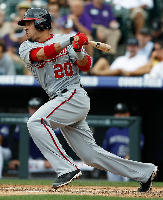 . Washington Nationals\' Ian Desmond follows the flight of his single against the Colorado Rockies in the fourth inning of a baseball game in Denver, Thursday, June 13, 2013. (AP Photo/David Zalubowski)