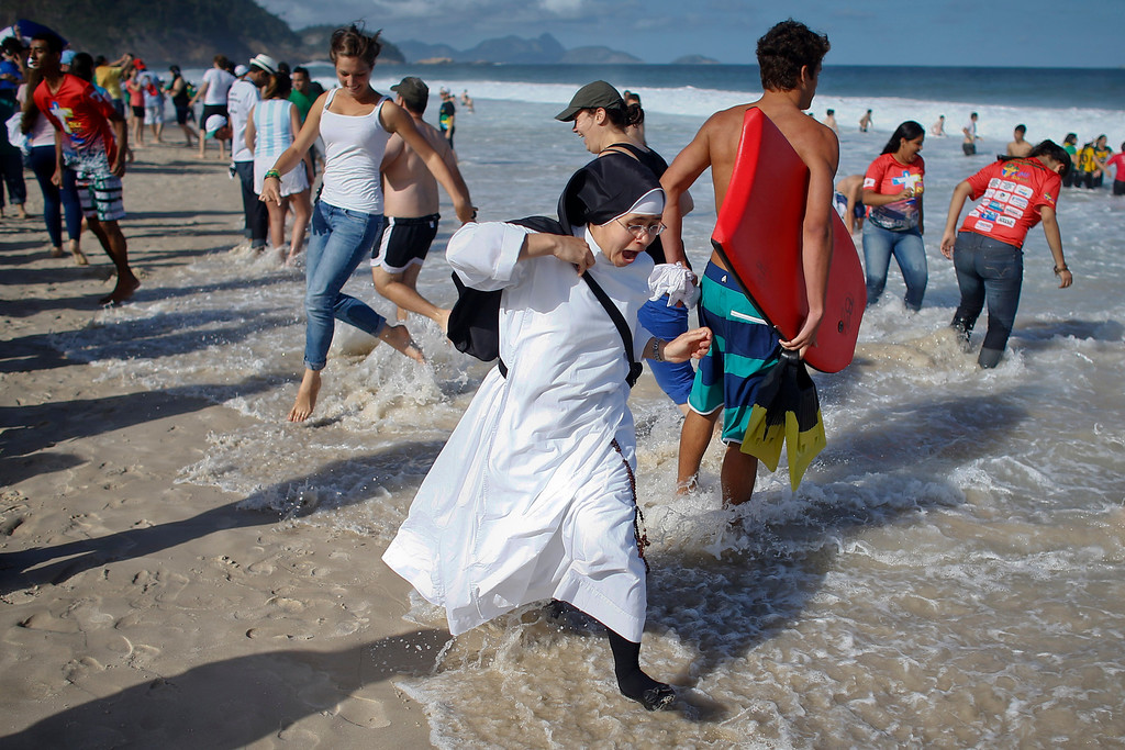 . A nun reacts as the tide comes in fast on Copacabana beach in Rio de Janeiro, Brazil, Saturday, July 27, 2013. Pope Francis was to preside over an evening vigil service on Copacabana beach that was expected to draw more than 1 million young people. (AP Photo/Victor R. Caivano)