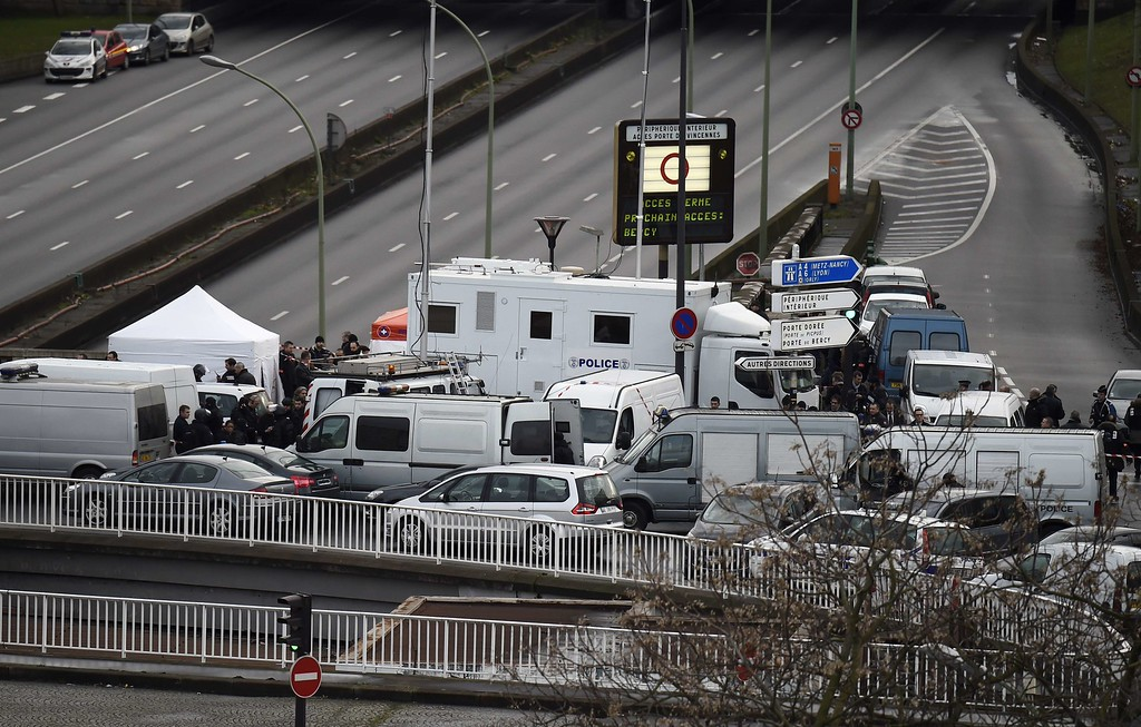 ". A photo taken on January 9, 2015 shows French police forces gathered by empty vehicles on a bridge above the ""peripherique\"" (circular road) at Porte de Vincennes, eastern Paris, after at least one person was injured when a gunman opened fire at a kosher grocery store on January 9 and took at least five people hostage, sources told AFP. The attacker was suspected of being the same gunman who killed a policewoman in a shooting in Montrouge in southern Paris on January 8.   AFP PHOTO / ERIC  FEFERBERG/AFP/Getty Images"