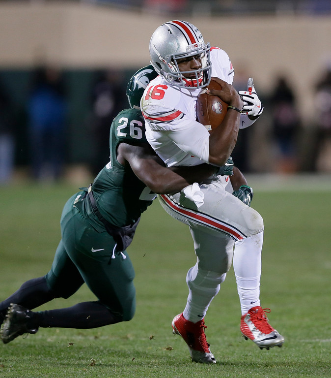. Ohio State quarterback J.T. Barrett (16) is stopped by Michigan State safety RJ Williamson (26) during the second half of an NCAA college football game in East Lansing, Mich., Saturday, Nov. 8, 2014. Barrett threw for three touchdowns and ran for two as 14th-ranked Ohio State won 49-37. (AP Photo/Carlos Osorio)