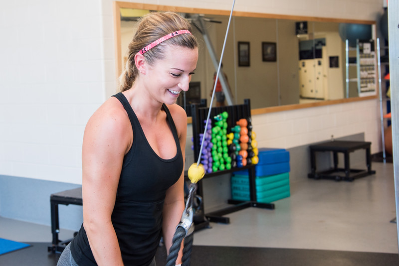 Student McKenna Kimble doing some tricep extensions in the Dugan Wellness Center during summer II.