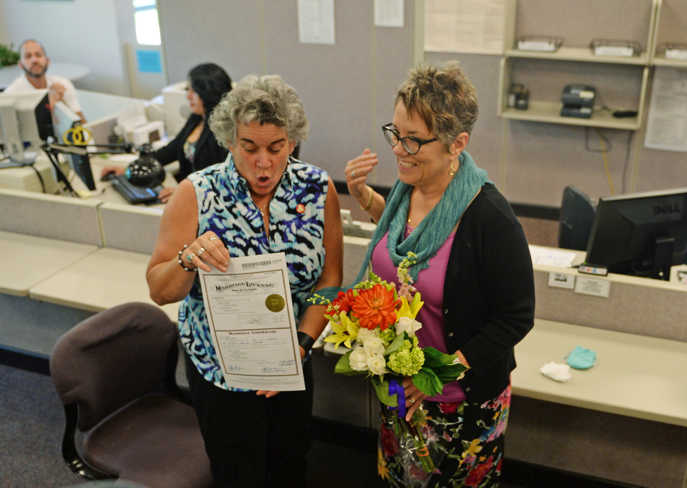 . Newlyweds Bylo Farmer, left, and Angie Holley, of Boulder, show off their marriage license issued this morning at the Boulder County Clerk and Recorder\'s Office, June 26, 2014. The state of Utah\'s same-sex marriage ban was struck down by the 10th Circuit Supreme Court. (Photo by RJ Sangosti/The Denver Post)