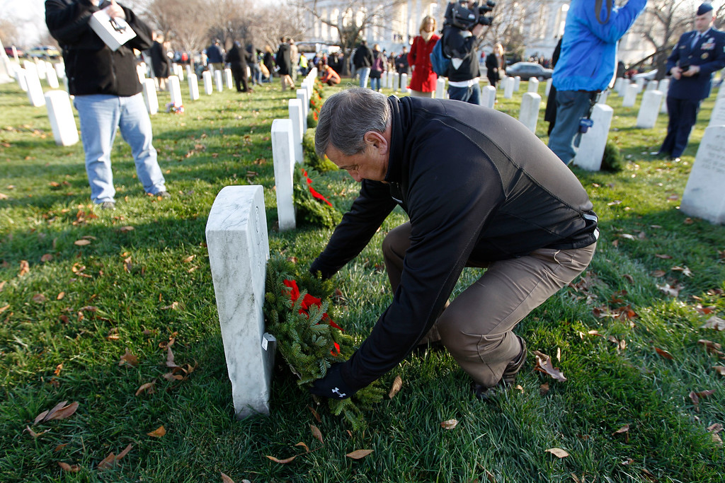 . Gov. Paul LePage of Maine lays a holiday wreaths over the grav of a fallen soldiers at Arlington National Cemetery in Washington Saturday Dec. 10, 2011, during Wreaths Across America Day. (AP Photo/Jose Luis Magana)