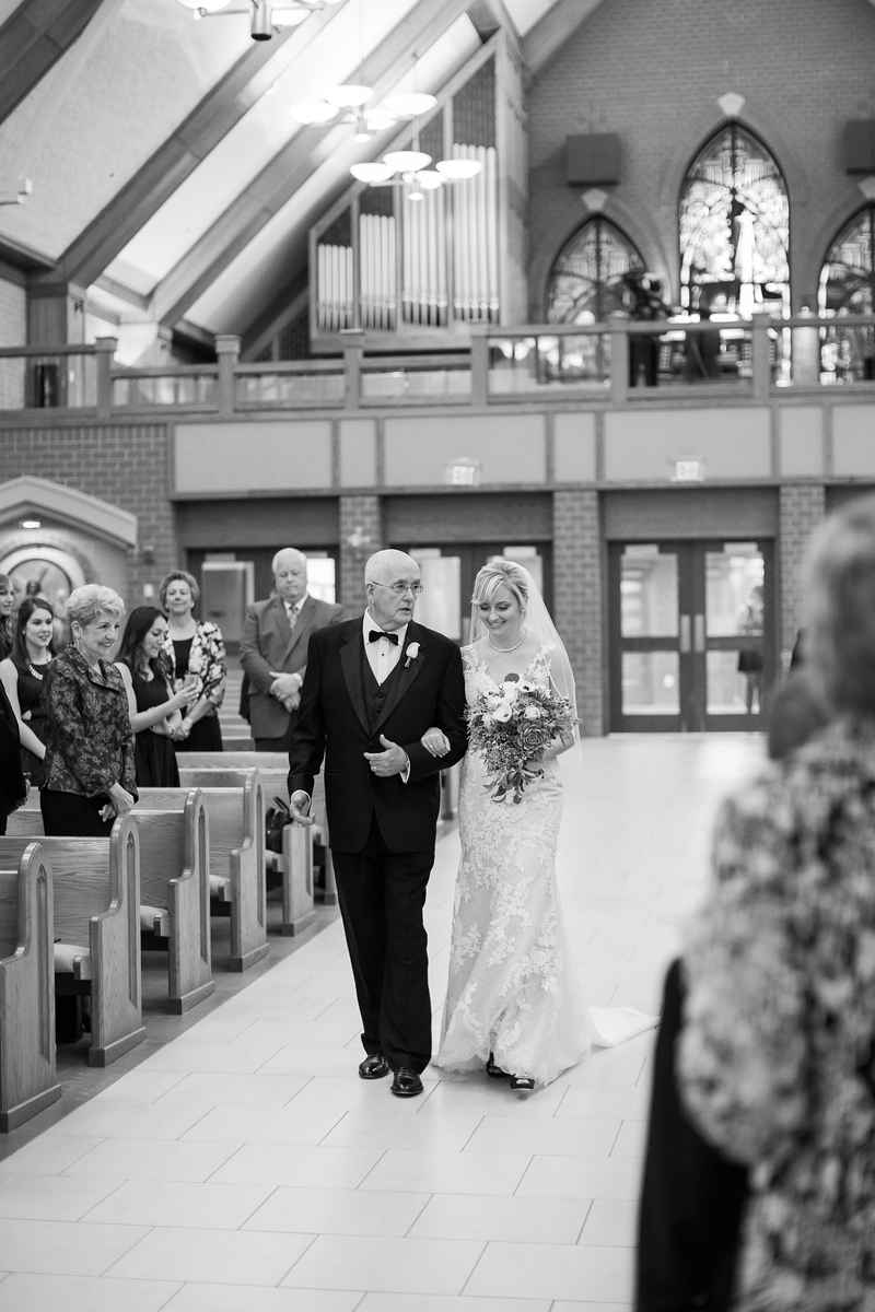 Meg's father walks her down the aisle at her Bluemont Vineyard wedding. Photos by the best Washington DC wedding photographer Jalapeno Photography. The Catholic wedding ceremony was at St. Theresa Catholic Church in Ashburn, VA.