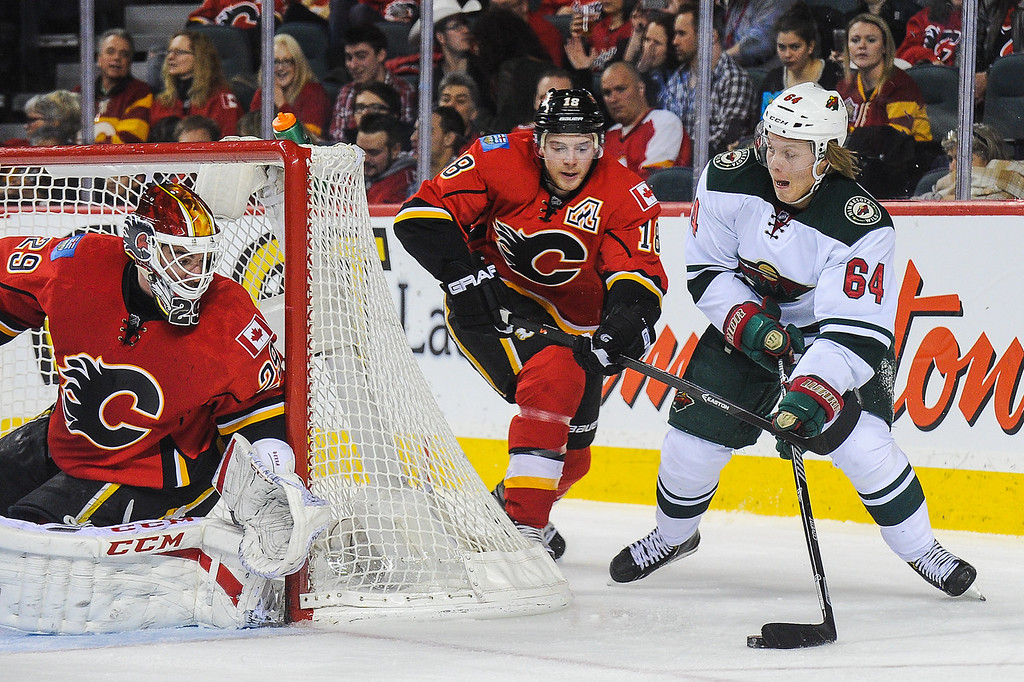 . Reto Berra #29 of the Calgary Flames defends net as Mikael Granlund #64 of the Minnesota Wild attempts a wrap-around during an NHL game at Scotiabank Saddledome on February 1, 2014 in Calgary, Alberta, Canada. (Photo by Derek Leung/Getty Images)