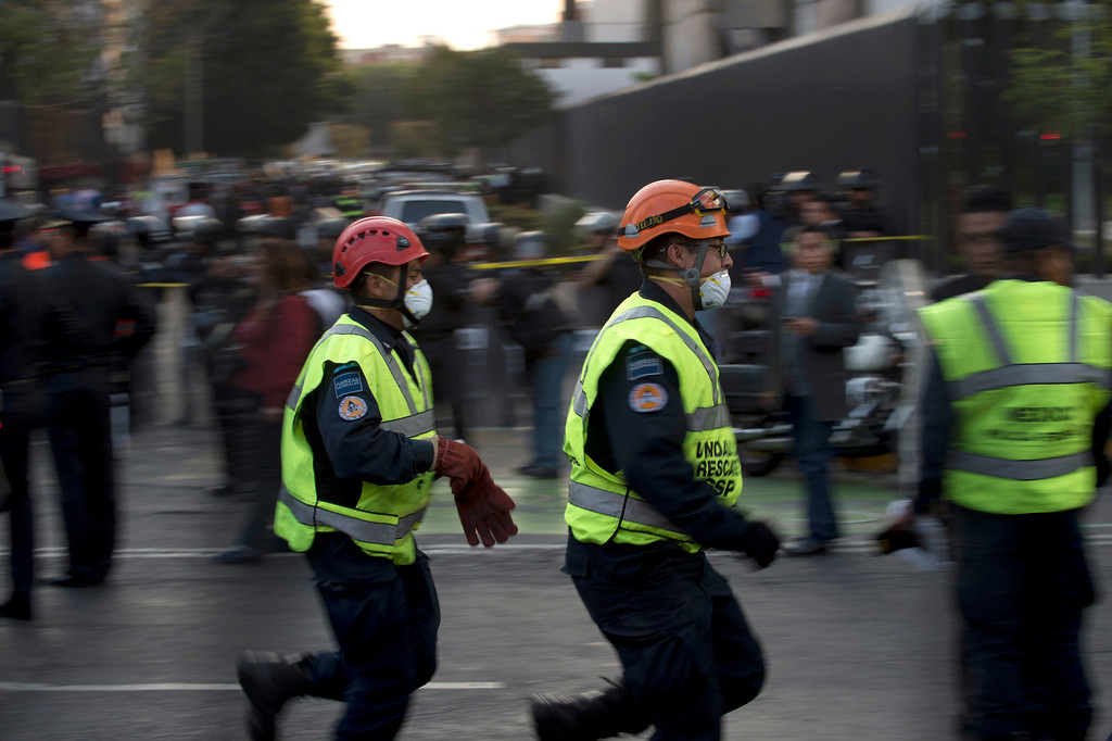 . Rescue workers head for the skyscraper that houses the headquarters of state-owned Mexican oil giant Pemex in Mexico City on January 31, 2013, following a blast inside the building.     YURI CORTEZ/AFP/Getty Images