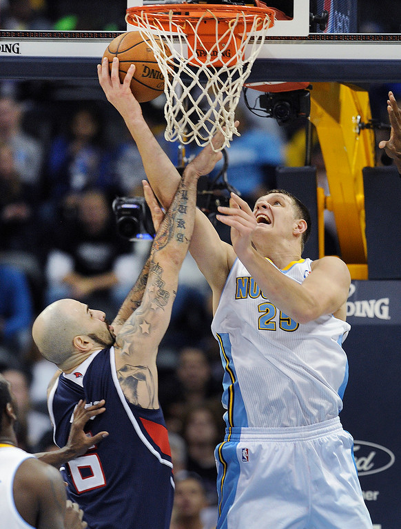 . Denver center Timofey Mozgov (25) worked under the basket against Atlanta center Pero Antic (6) in the first half.   Photo By Karl Gehring/The Denver Post