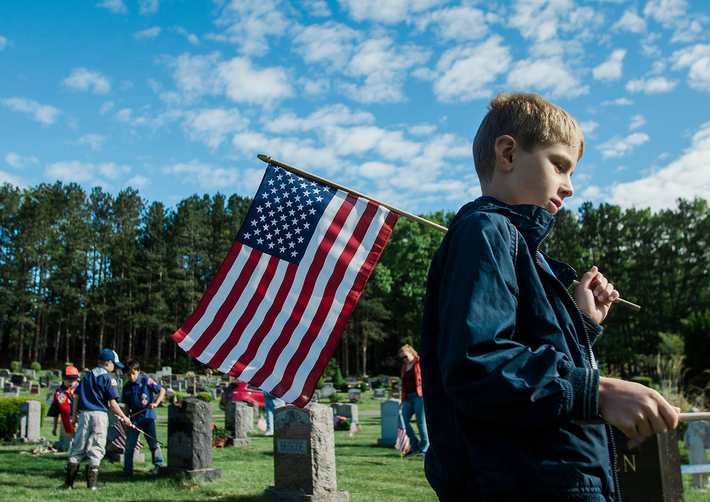. Karl Uschold, 8, from Cub Scout Pack 3, flags the graves of veterans at St. Leo\'s Cemetery in Leominster on Saturday, May 27, 2017 ahead of Memorial Day weekend. SENTINEL & ENTERPRISE / Ashley Green