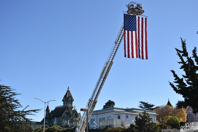 A U.S. Flag hangs from the ladder of a Humboldt bay Fire Department hook and ladder engine with the Carson Mansion in the background.