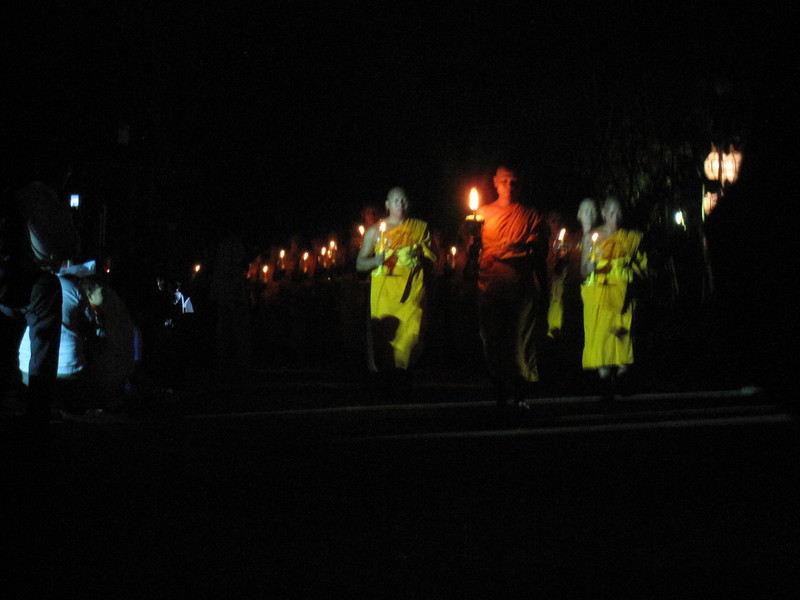 The bunches of monks that were walking around with a candle stick in their hands.