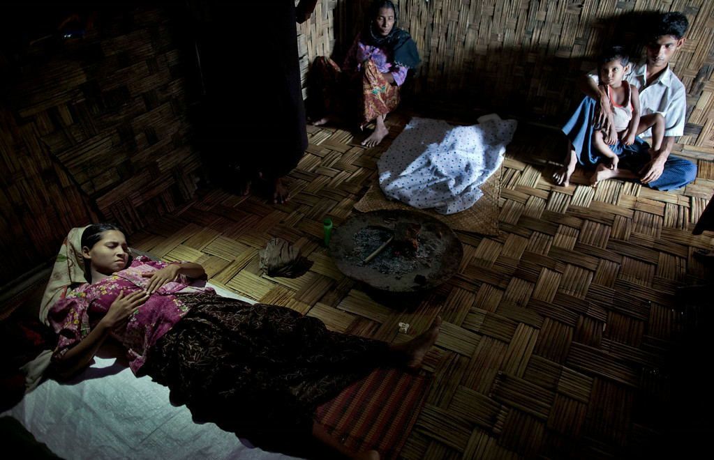 . In this June 27, 2014 photo, Shamshu Nahad, left, lies on the floor, bleeding profusely after enduring complications during child birth in Dar Paing, a camp for Rohingya Muslims in north of Sittwe, Rakhine state, Myanmar. The corpse of her tiny daughter, who died hours after the delivery, is covered with a white cloth, far middle. Her 25-year-old\'s husband Mohammed Shafiq, right, her son Mohammed Rohim, second from right, and mother Hasina, second from left, sit along the wall of the familiesí makeshift bamboo hut in a camp for Rohingya refugees who were displaced during Buddhist-led violence in 2012. (AP Photo/Gemunu Amarasinghe)