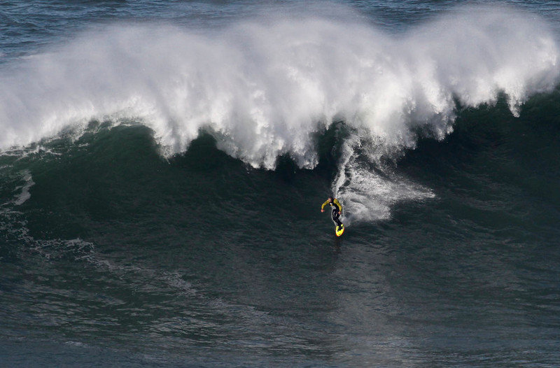 . US surfer Garrett McNamara rides a wave at Praia do Norte beach in Nazare, Portugal, Tuesday, Jan. 29, 2013. McNamara is said to have broken his own world record for the largest wave surfed when he caught a wave reported to be around 100ft off the coast of Nazare on Monday. If the claims are verified, it will mean that McNamara, who was born in Pittsfield, Massachusetts but whose family moved to Hawaii\'s North Shore when he was aged 11, has beaten his previous record, which was also set at Nazare, of 78 feet in November 2011. (AP Photo/Francisco Seco)