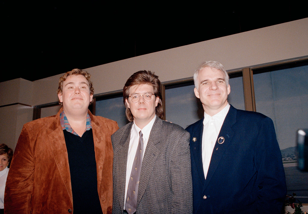 ". John Candy, left, John Huges and Steve Martin stand together during a news conference for ""Planes, Trains & Automobiles\"" in 1987. Great Lakes Science Center presents a double feature of \""Uncle Buck\"" and \""Planes, Trains & Automobiles\"" on Nov. 25 in the Cleveland Clinic DOME Theater. For more information, visit greatscience.com/explore/cleveland-clinic-dome-theater/take-two-double-feature-series. (Associated Press file)"