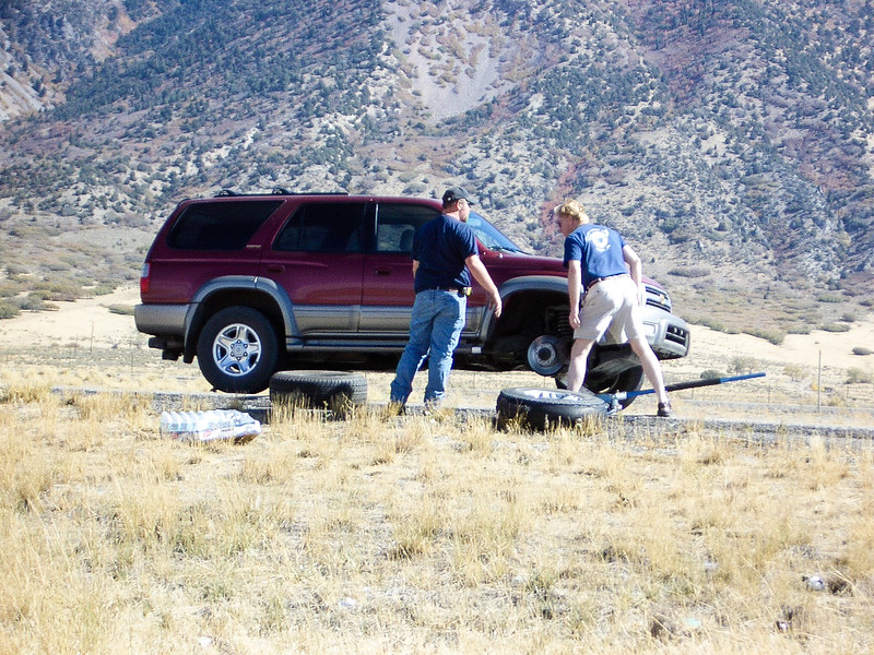Two men changing a tires on the side of an Interstate.