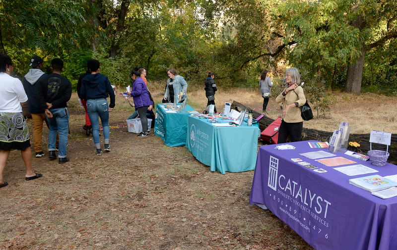 "About 40 people take part in a silent walk to place flower petals in the creek during the ""Flowers on the Creek"" Domestic violence victims remembrance at the One Mile Recreation Area of Bidwell Park in Chico, Calif. Thursday, Oct. 4, 2018.  The program, sponsored by Catalyst Domestic Violence Services, Chico Safe Place, Butte College Safe Place and Wellness Program, and the Butte County Child Abuse Prevention Council is in recognition of October as Domestic Violence Awareness Month. (Bill Husa -- Enterprise-Record)"