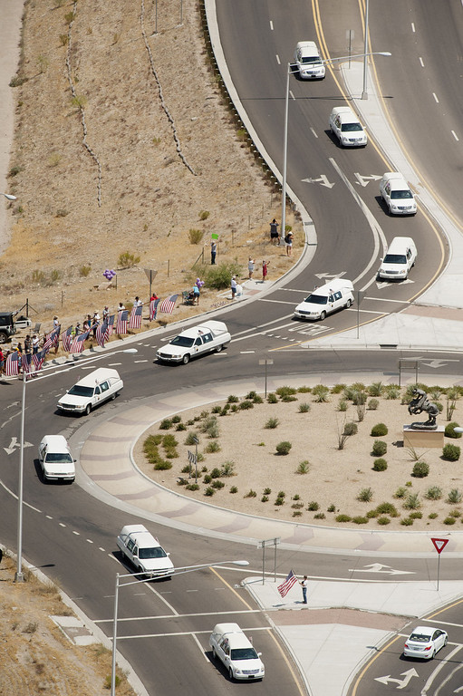. A procession makes its way under escort by the Joint Arizona Honor Guard, for the 19 fallen firefighters of the Granite Mountain Hotshots crew on July 7, 2013 in Phoenix, Arizona. The firefighters are transported by 19 hearses, each accompanied by motorcycle escorts from various agencies from Phoenix, Arizona to Prescott, Arizona. Nineteen of the twenty member crew died battling a fast-moving wildfire near Yarnell, Arizona on Sunday June 30th. (Photo by Laura Segall/Getty Images)