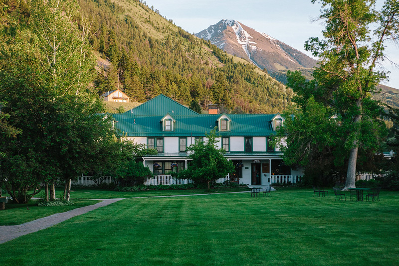 Green and white lodge with mountain backdrop