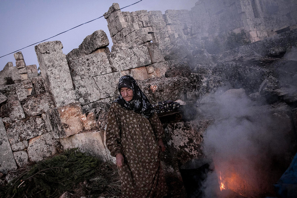 . In this Thursday, Sept. 26, 2013 photo, a displaced Syrian woman cooks a meal for dinner at sunset near Kafer Rouma, amid ancient ruins used as temporary shelter by those families who have fled from the heavy fighting and shelling in the Idlib province countryside of Syria.(AP Photo)