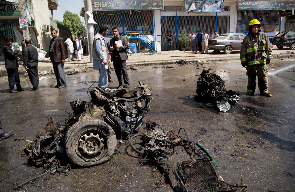 . An Afghan fireman stands next to the debris of a car at the scene where a suicide car bomber attacked a NATO convoy in Kabul, Afghanistan, Thursday, May 16, 2013. (AP Photo/Anja Niedringhaus)