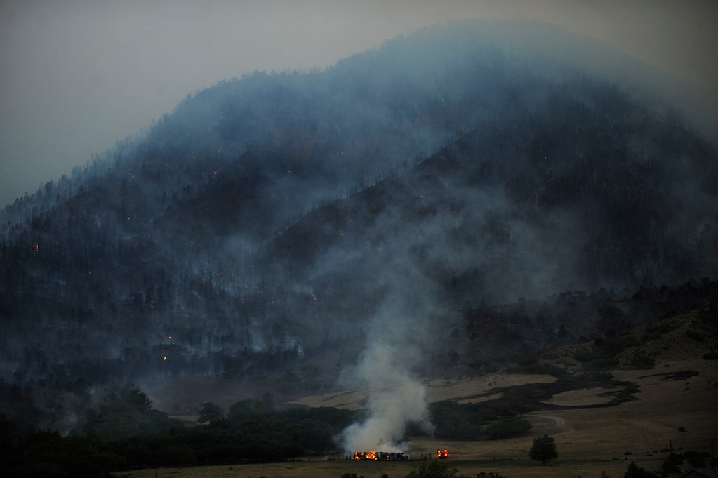 . An emergency vehicle stops next to a burning home in the foothills of Colorado Springs on June 26th, 2012. Helen H. Richardson, The Denver Post