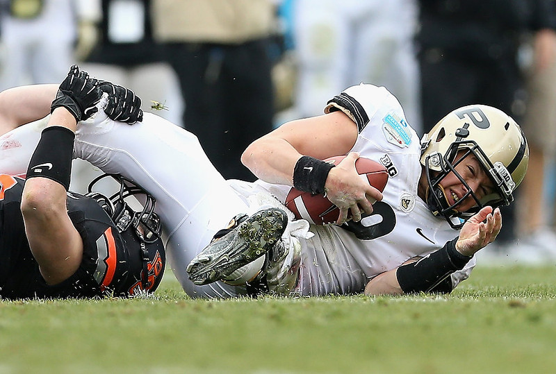 . Robert Marve #9 of the Purdue Boilermakers is tackled by Caleb Lavey #45 of the Oklahoma State Cowboys during the Heart of Dallas Bowl at Cotton Bowl on January 1, 2013 in Dallas, Texas.  (Photo by Ronald Martinez/Getty Images)