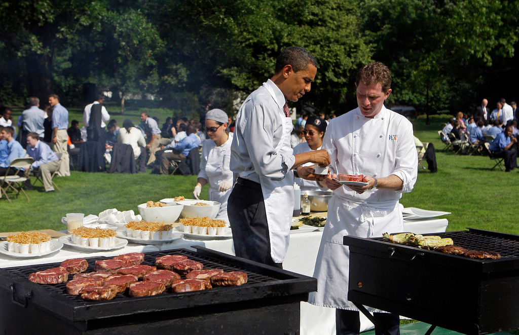 . President Barack Obama, left, receives grilling tips from Chef Bobby Flay on the South Lawn of the White House, Friday, June 19, 2009, in Washington during an event in conjunction with fatherhood and mentoring. (AP Photo/Haraz N. Ghanbari)