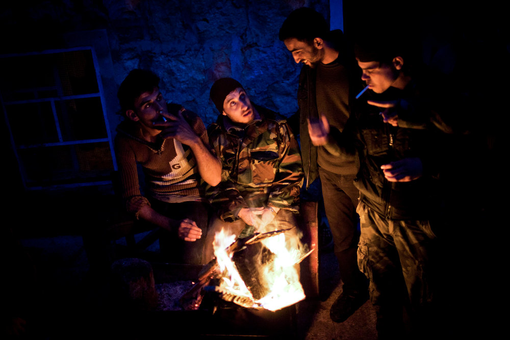 Description of . In this Wednesday, Dec. 12, 2012 photo, Free Syrian Army fighters warm themselves in the northern province of Aleppo, Syria. Syria's civil war has killed more than 40,000 people. (AP Photo/Manu Brabo)