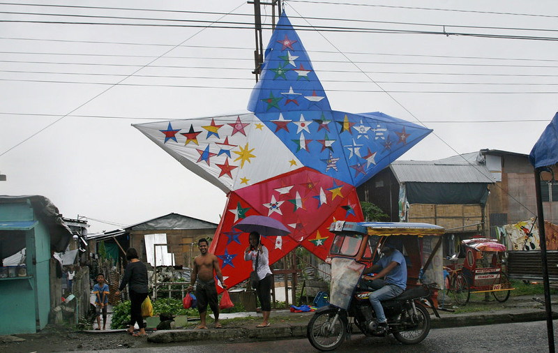 . A motorized tricycle (bottom R) rides past a Christmas decorative lantern in Tacloban, in the central Philippines, on December 24, 2014. Thousands of residents of the typhoon-weary city of Tacloban in the mainly Catholic Philippines got ready on December 24 to mark their second Christmas in ruins following two giant storms.      MARLON TANO/AFP/Getty Images
