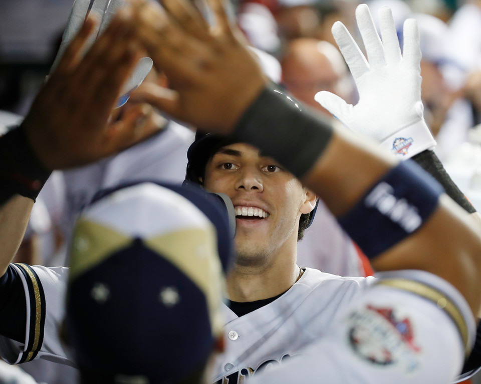 . Milwaukee Brewers Christian Yelich (22) celebrates his solo home run in the dugout in the eighth inning during the Major League Baseball All-star Game, Tuesday, July 17, 2018 in Washington. (AP Photo/Alex Brandon)