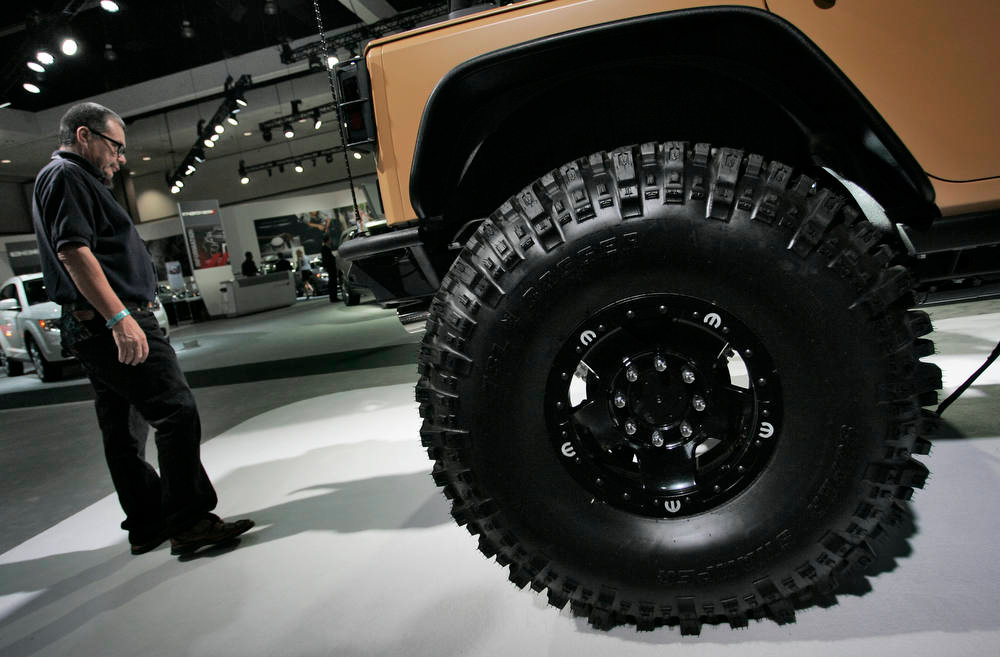 Description of . An attendee looks at a Mopar Concept Jeep Wrangler Sand Trooper automobile, produced by Chrysler Group LLC, during the LA Auto Show in Los Angeles, California, U.S., on Wednesday, Nov. 28, 2012. The LA Auto Show is open to the public Nov. 30 through Dec. 9. Photographer: Jonathan Alcorn/Bloomberg
