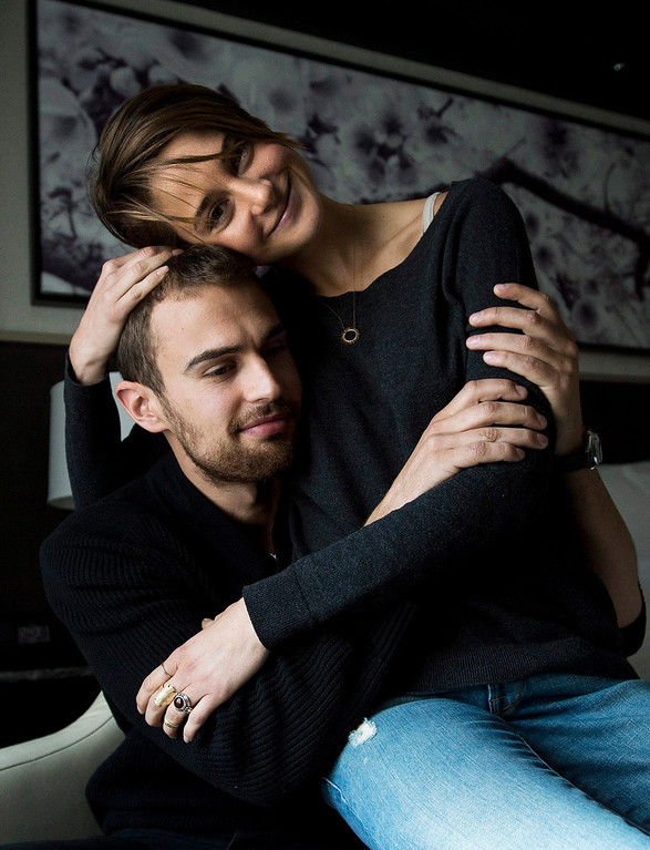 """. In this Thursday, March 6, 2014 file photo, actors Theo James, left, and Shailene Woodley pose for a photograph as they promote the movie \""""Divergent,\"""" in Toronto. The 22-year-old \""""Divergent\"""" star gives hearty embraces often more than one - to everyone she meets. Woodley and James star in the anticipated first film in the young adult trilogy by author Veronica Roth. (AP Photo/The Canadian Press, Nathan Denette, file)"""