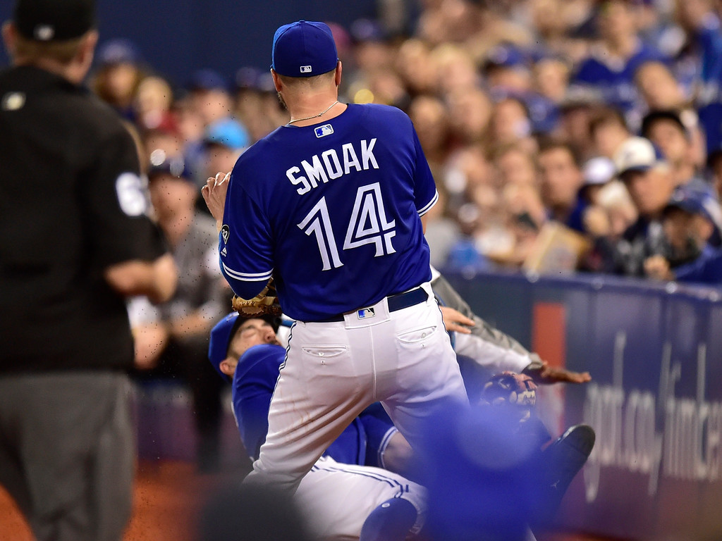 . Toronto Blue Jays right fielder Randal Grichuk (15) collides with a security guard in foul territory as Jays first baseman Justin Smoak (14) moves in during fourth inning baseball action against the Cleveland Indians in Toronto, Sunday, Sept. 9, 2018. (Frank Gunn/The Canadian Press via AP)