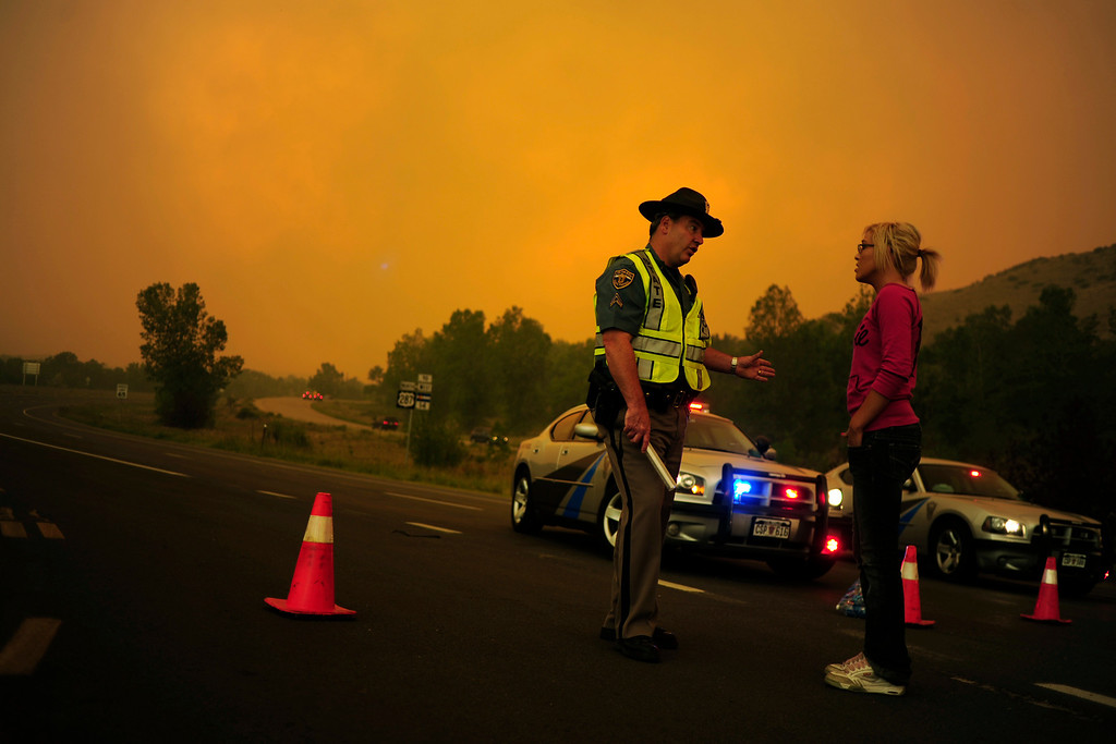 . Trooper Kenner speaks with Brittany Harrington at a road closure on Highway 287 as the High Park fire burns west of Fort Collins and Loveland on Sunday, June 10, 2012. Harrington\'s home was blocked off due to the road closure, but she was able to walk with her boyfriend to their house. The rapidly growing High Park fire is now burning an estimated 2,000 to 3,000 acres west of Fort Collins and Loveland, according to the Larimer County Sheriff�s Office. AAron Ontiveroz, The Denver Post