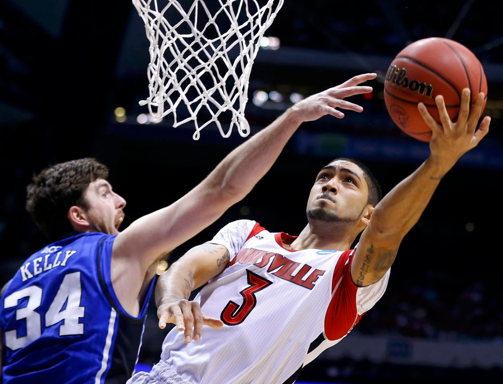 Description of . Louisville Cardinals guard Peyton Siva (3) goes to the basket against Duke Blue Devils forward Ryan Kelly (34) in the first half during their Midwest Regional NCAA men's basketball game in Indianapolis, Indiana, March 31, 2013. REUTERS/Jeff Haynes