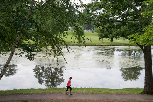 06/24/19 Wesley Bunnell | Staff A walker makes her way around the pond on a warm Monday afternoon at Stanley Quarter Park on June 24, 2019.