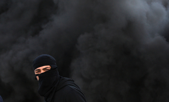 . A Palestinian wears a mask during clashes with the Israeli army north of the West Bank city of Jenin in support to the Palestinian prisoners on hunger strike in Israeli jails and against the administrative detention, Friday, Feb. 15, 2013. (AP Photo/Mohammed Ballas)