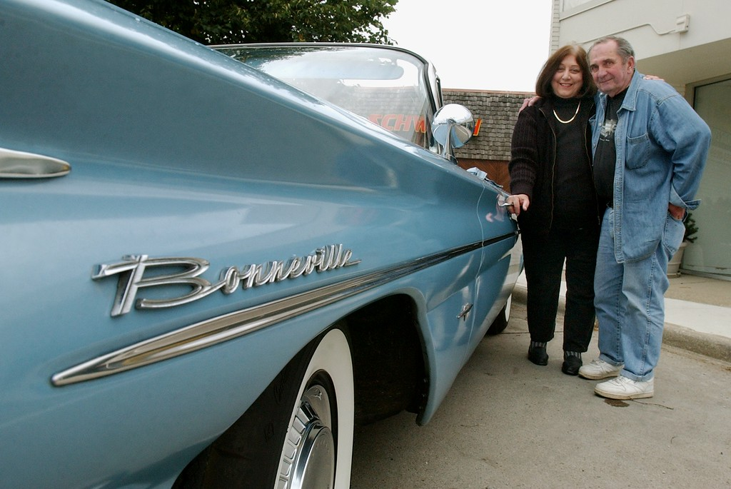 . Betty, left, and Bob Kessel of Bloomfield Township, Mich., stand next to their 1960 Pontiac Bonneville.  Photo taken on Friday, August 13, 2004, in Birmingham, Mich.  They plan on parking their car along Woodward Avenue during the upcoming Dream Cruise.