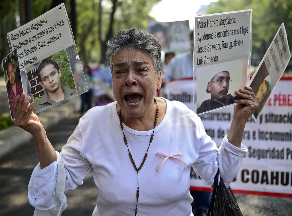 . A woman shows pictures of her four sons missing due to the drug war in the country, during a protest in Mexico City on May 10, 2013. A group of mothers and relatives of children and youngs missing, demand to the Government the investigation of the crimes. Ronaldo Schemidt/AFP/Getty Images