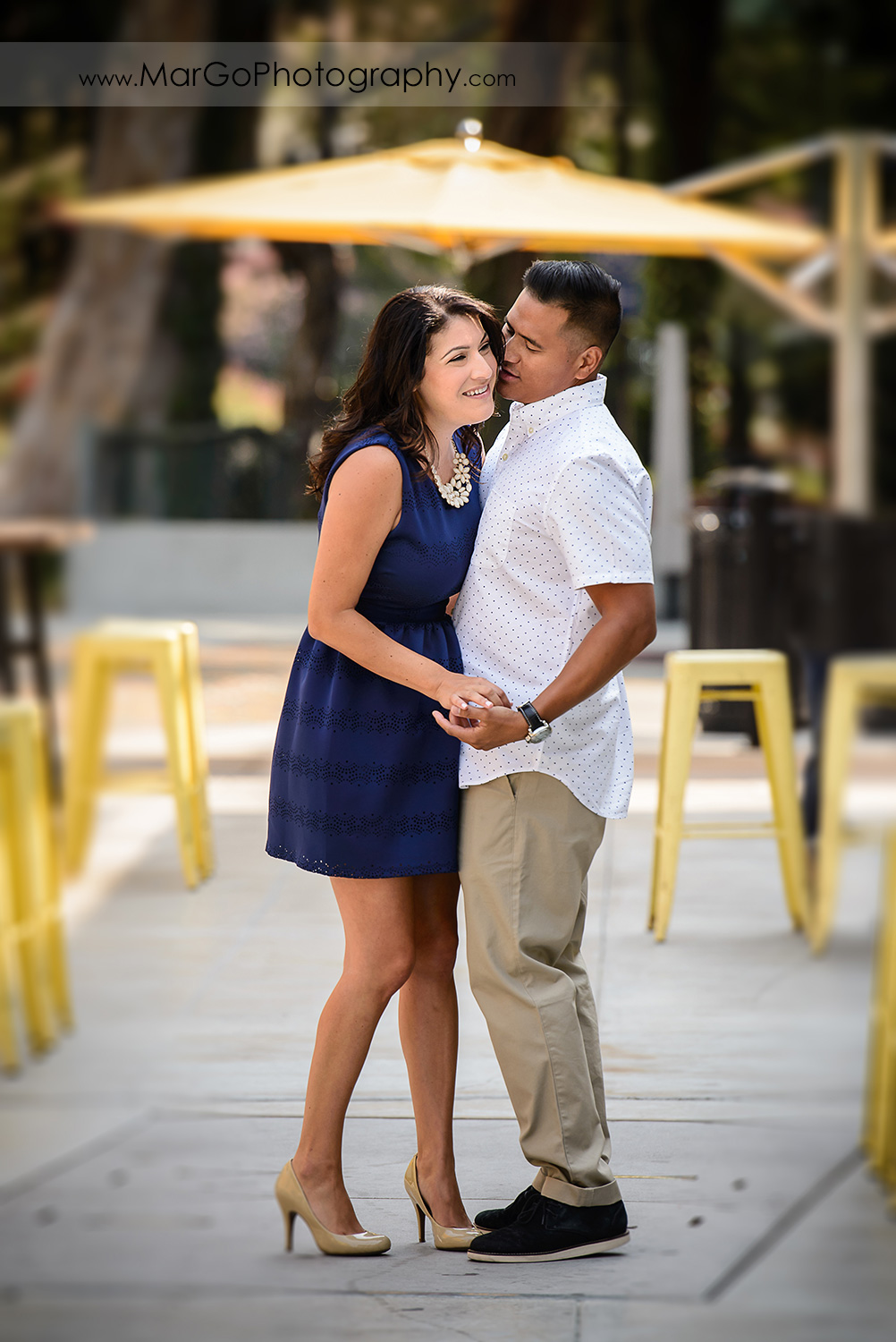 woman in blue dress and man in white shirt dancing during engagement session at San Pedro Square Market in San Jose