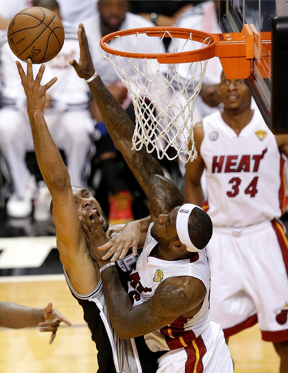 . San Antonio Spurs forward Tim Duncan and Miami Heat forward LeBron James (6) collide under the basket during the first half of Game 2 of the NBA Finals basketball series, Sunday, June 9, 2013, in Miami. Heat\'s Ray Allen (34) watches. (AP Photo/Wilfredo Lee)