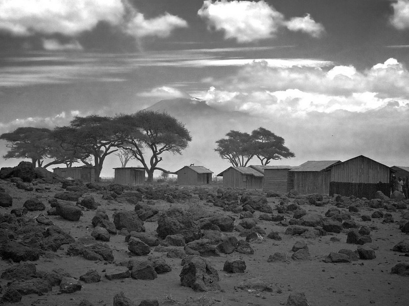 The Masai live in their bomas, but time is catching up on them, and even the living conditions change from houses of mud to these wooden or brick houses. The rocks are lava remains from one of Kilimanjaro's eruptions. (Foto: Geir)