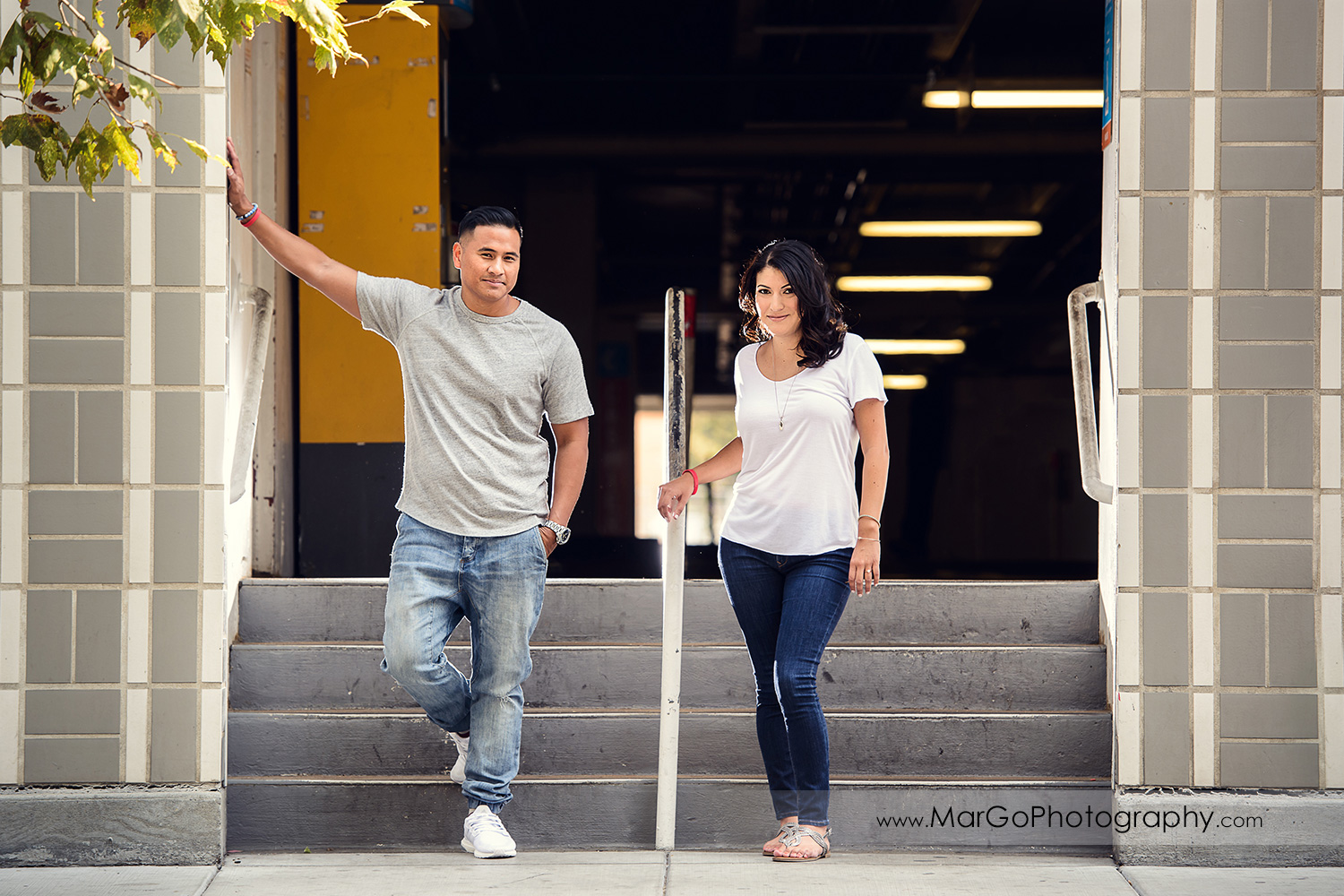 full body portrait of couple in white t-shirts and jeans looking into camera during engagement session in entrance to San Pedro Square Market garage in San Jose