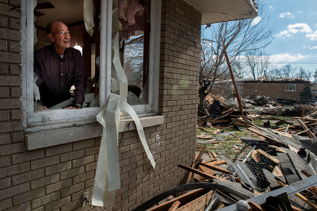 . Chuck Phillips looks out at the destruction that tore off part of his roof and left houses around him destroyed after a tornado left a path of devastation through the north end of Pekin, Il.,Sunday, Nov. 17, 2013. Intense thunderstorms and tornadoes swept across the Midwest on Sunday, causing extensive damage in several central Illinois communities while sending people to their basements for shelter. (AP Photo/Journal Star, Fred Zwicky)